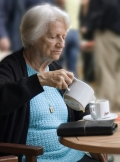 Picture of woman with dementia pouring tea.